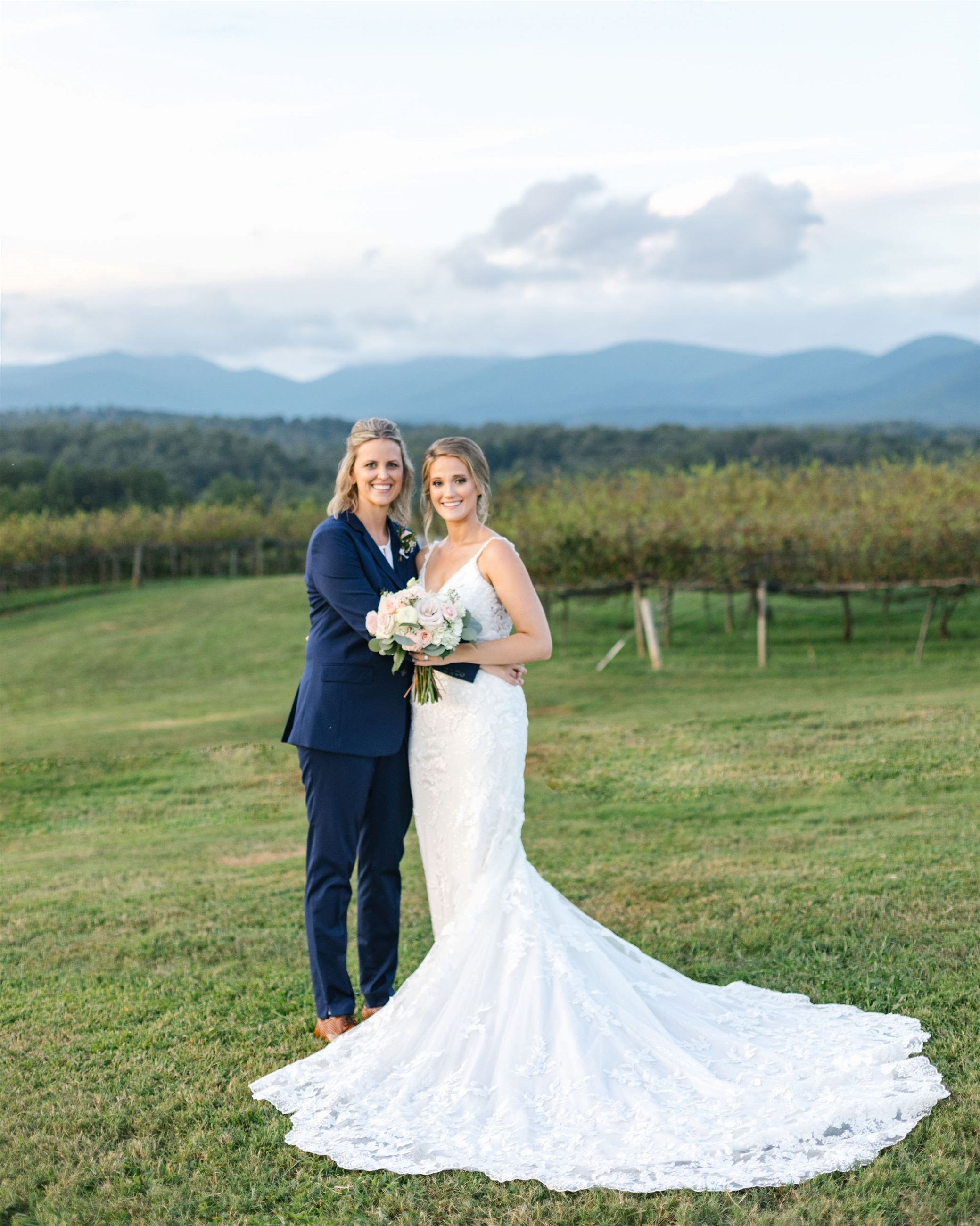 Two brides standing together in vineyard on wedding day