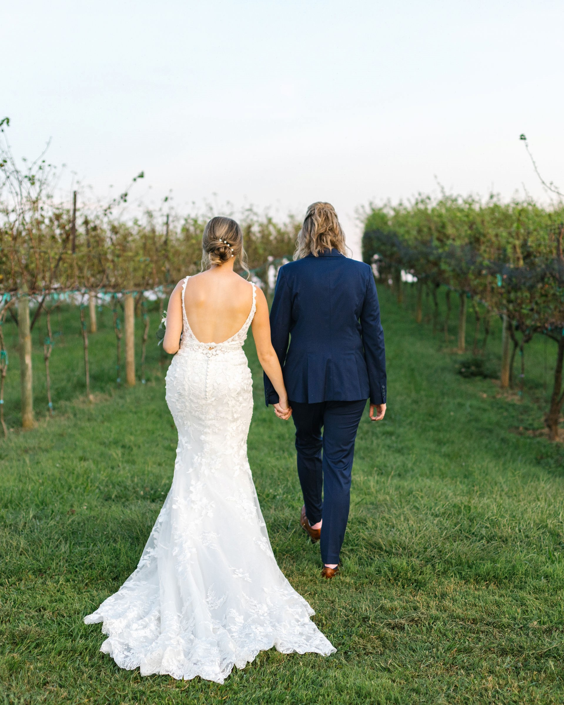 Two brides holding hands at their vineyard wedding