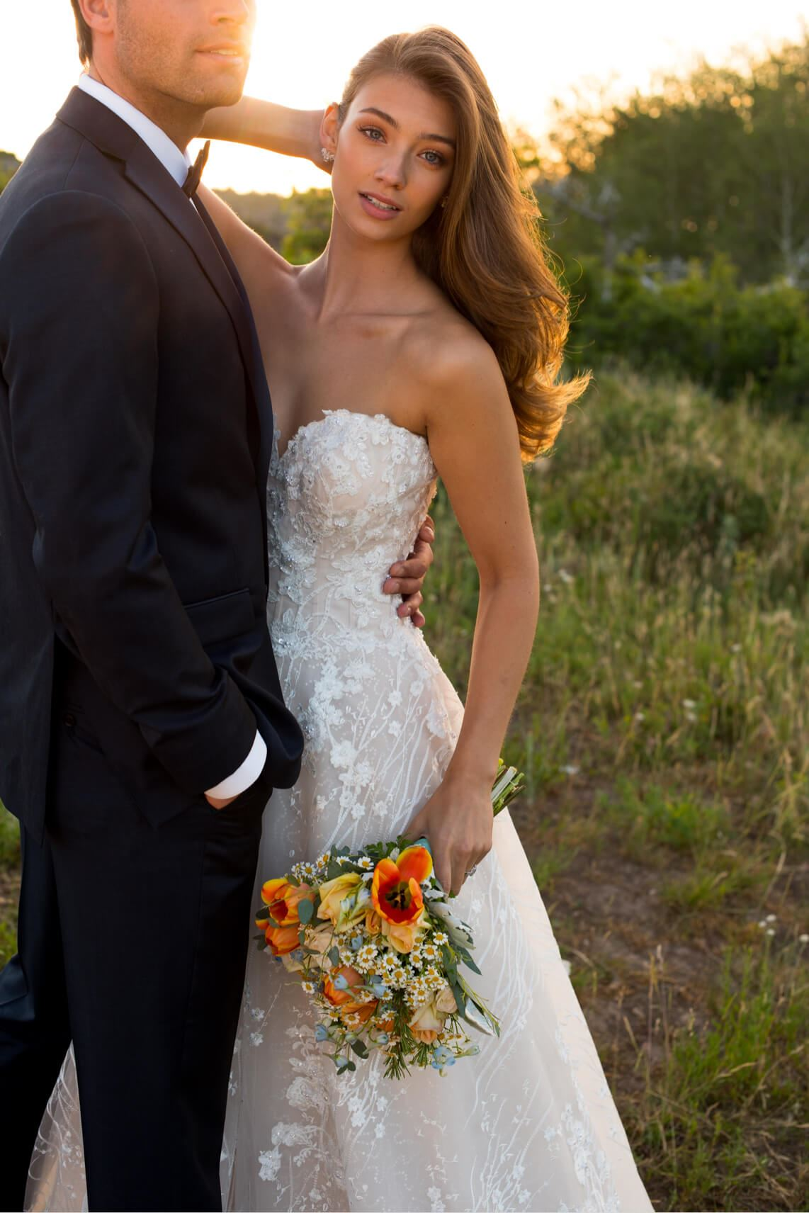 Brunette bride in Martin Thornburg wedding dress and groom in field