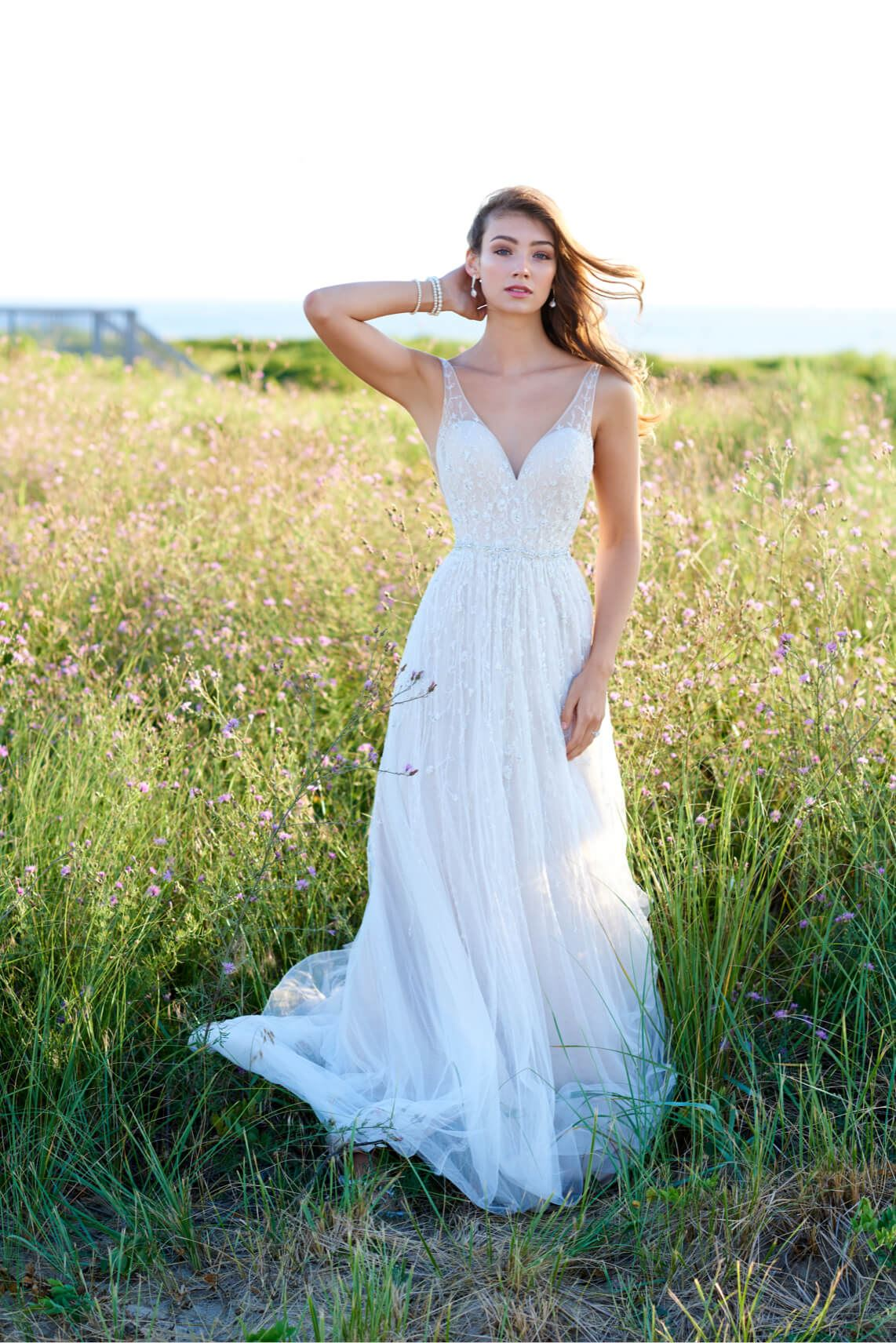Brunette model in field wearing wedding dress