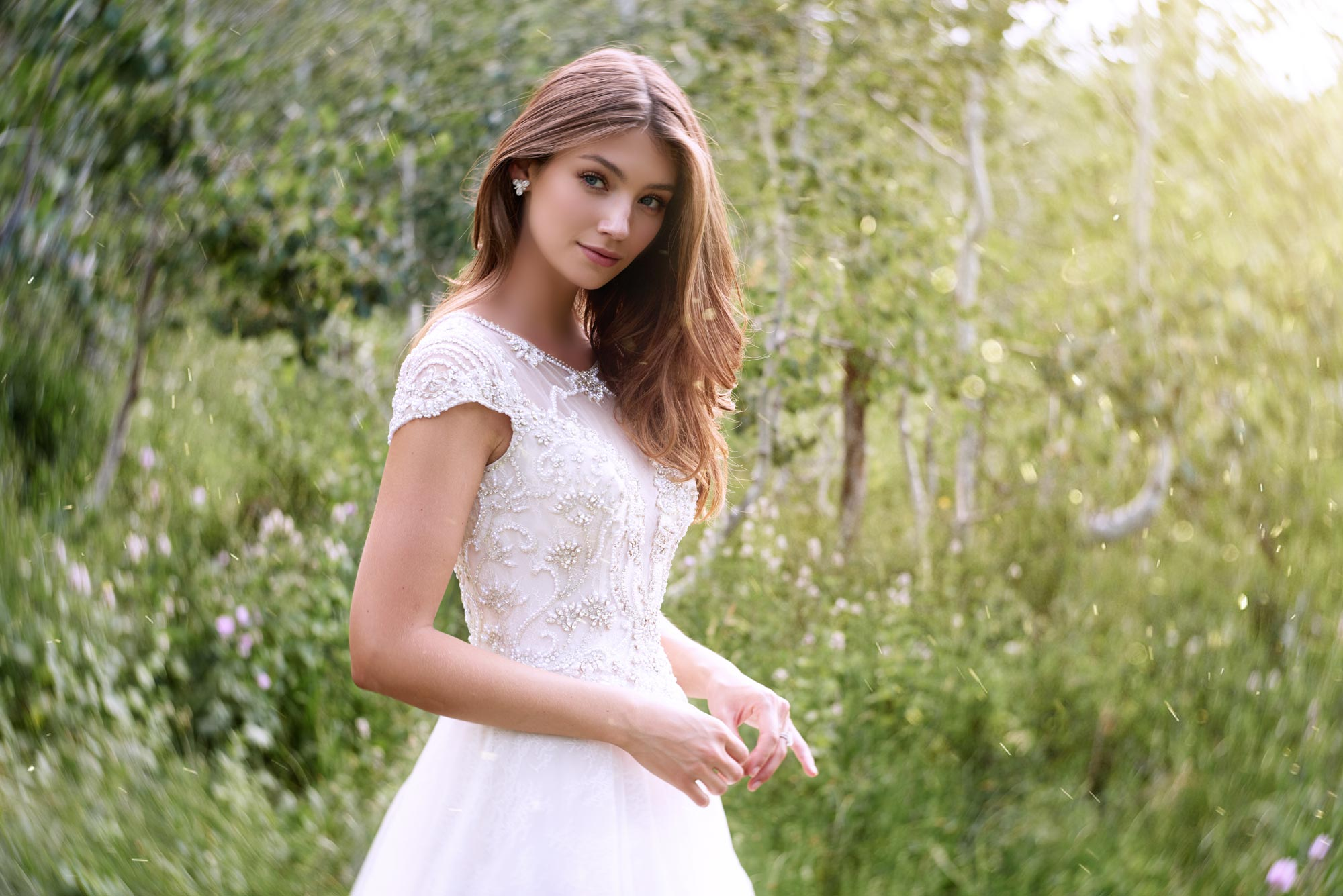 Brunette bride in field wearing short sleeve wedding dress