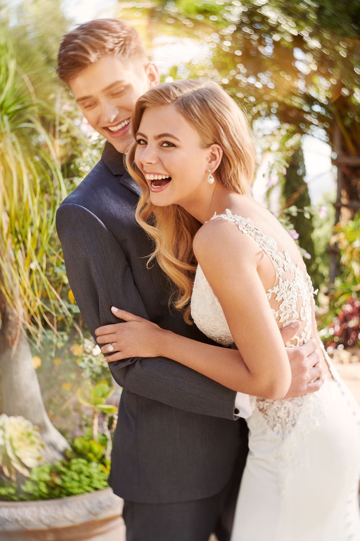 Blonde bride wearing lace wedding dress laughing with groom