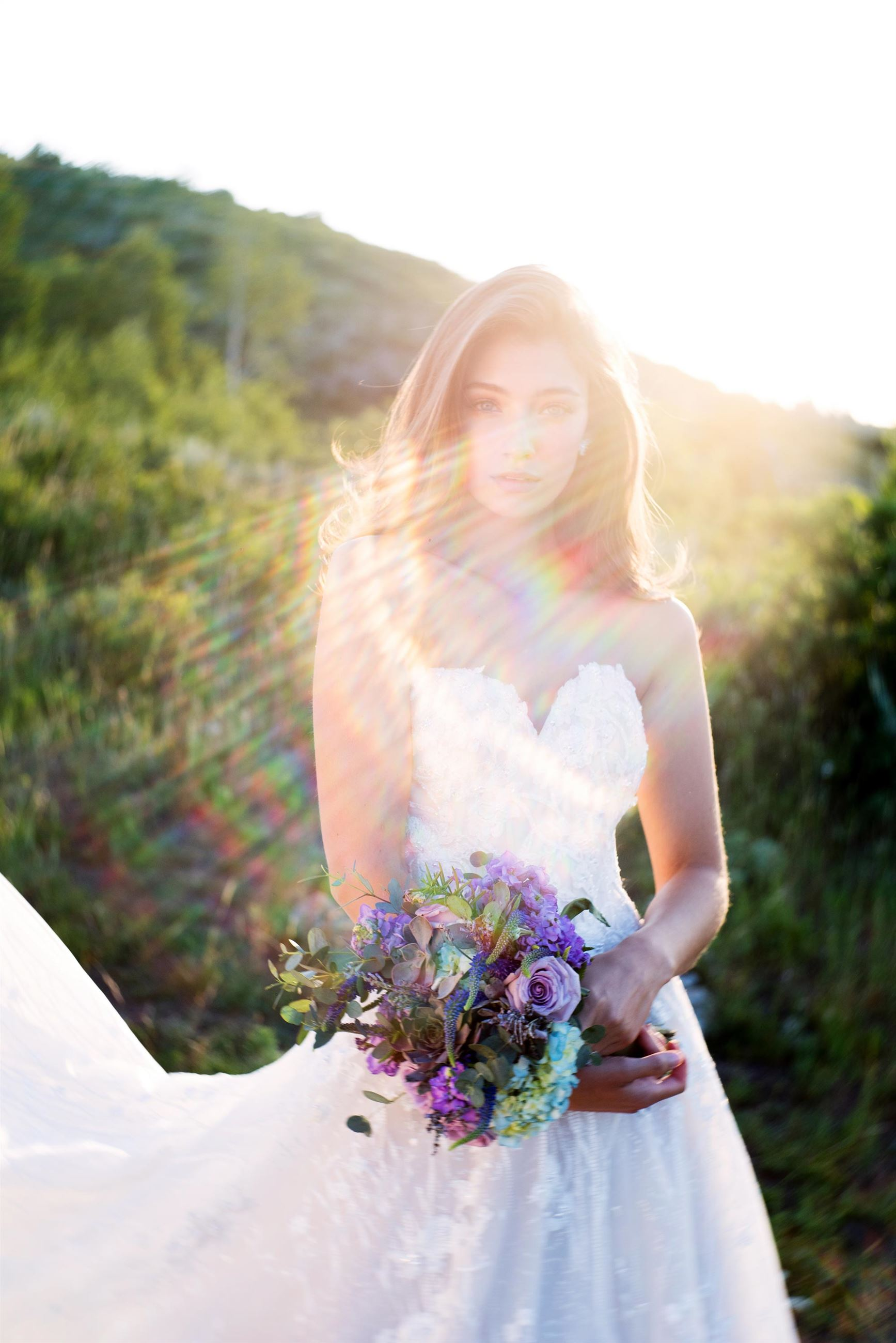 Brunette bride in strapless wedding dress holding flowers