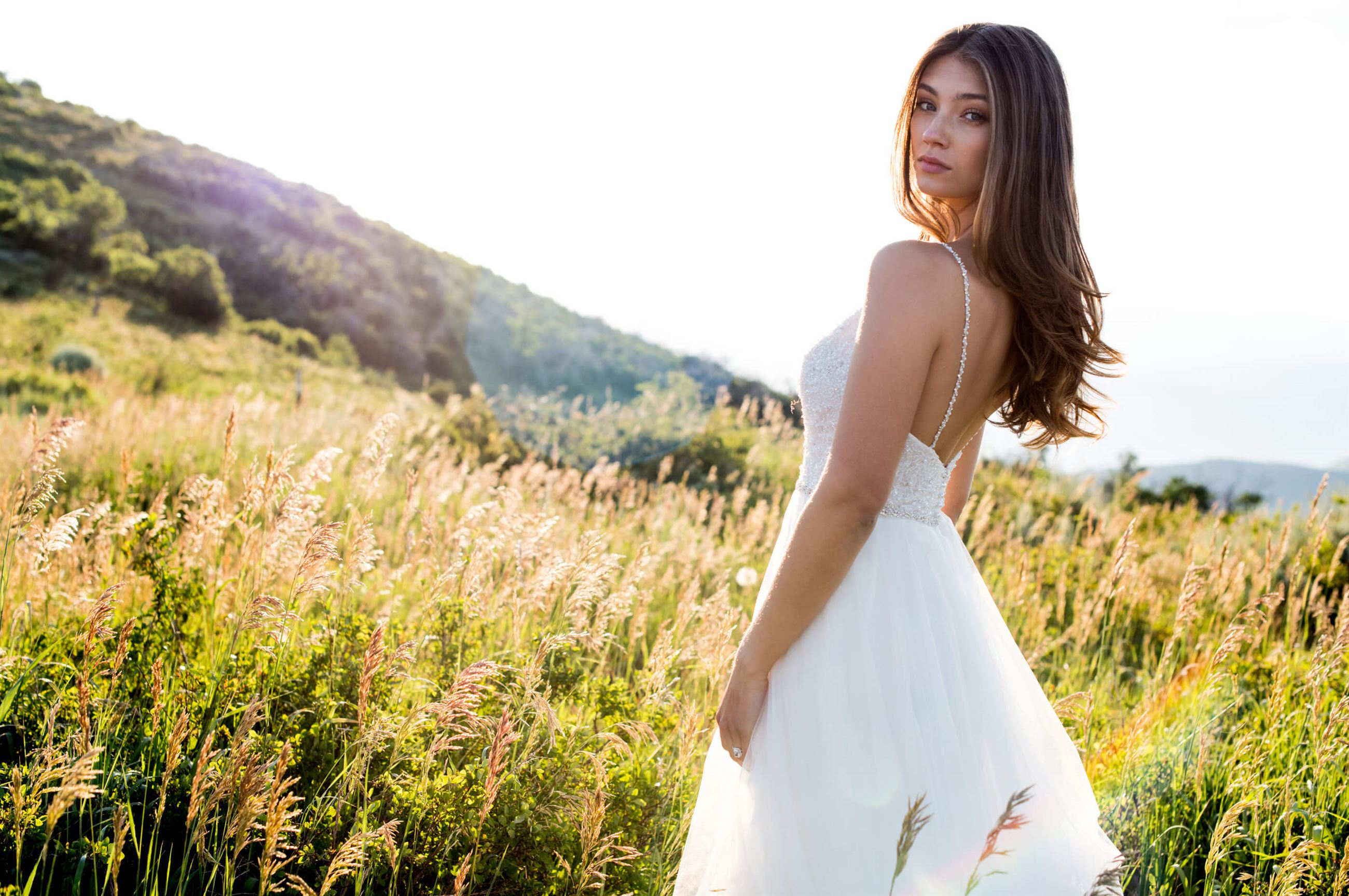 Brunette model in white wedding dress in field